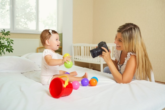 Mother  photographer photographing of her baby on camera.